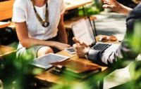 Kobieta i mężczyzna siedzący naprzeciwko siebie, na stoliku lezy laprop, tablet i telefon. Rozmawiają.